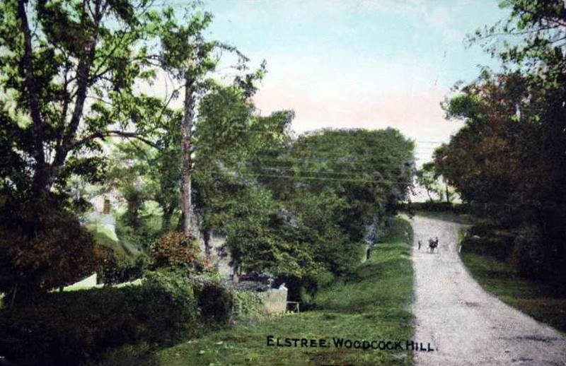 Woodcock Hill 1900s, looking down from the crossroads at Barnet Lane. The entrance to Woodcock Hill farm can just be seen on the right where the horse and cart is.